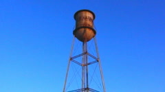 Rusty Old Water Tower Against Blue Sky Stock Footage