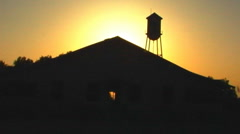 Sunset Behind Old Farmhouse With Water Tower 2 - stock footage