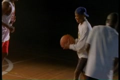 Three players passing a basketball around court - stock footage