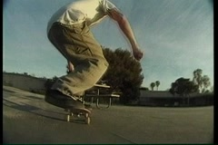 Distorted fisheye shot of skateboarder doing tricks and stunts on picnic table - stock footage
