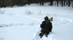 Kids play in snow digging tunnels, time lapse Stock Footage