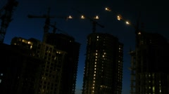 Cranes work on construction site after sunset, time lapse Stock Footage
