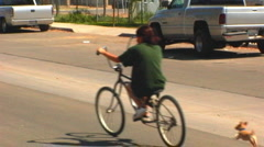 Little Dog Chases Girl On Bike In Small Town Stock Footage