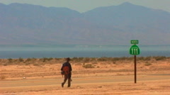Man Walks Hwy 111 - Salton Sea In Background 1 Stock Footage