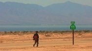 Man Walks Hwy 111 - Salton Sea In Background 1 Stock Footage