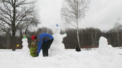 Kids and dad sculpt three snowmans, time lapse - stock footage