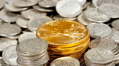 Pan from a single gold coin over silver coins - stock footage