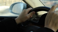 Hands holding the steering wheel of a car and tapping fingers in Moscow city Stock Footage