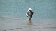 Beach scenic fisherman walks out of water on to rocky beach h264 Stock Footage