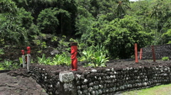 Tahiti red figures at a Marae pyramid Stock Footage