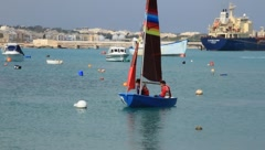 Small sailboat sailing past anchored boats on the Mediterranean Sea Stock Footage