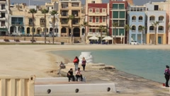 People walking along beach area near the city in Malta Stock Footage