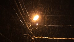 Lantern lamp and electrical lines in snowy midnight Stock Footage