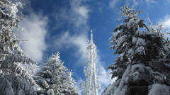 Cellular tower in snow on a blue sky background with clouds passing by Stock Footage