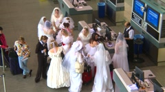 Odd scene - airport terminal many women in brides dresses checking in Stock Footage