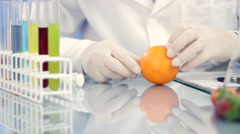Scientist hands in rubber gloves examining orange and writing results in notepad Stock Footage