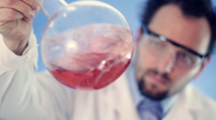 Male scientist mixing Volumetric flask with red liquid - stock footage