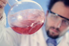 Male scientist mixing Volumetric flask with red liquid Stock Footage