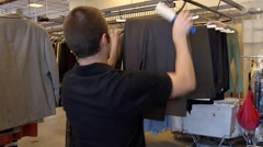 Employee De-linting garments - stock footage