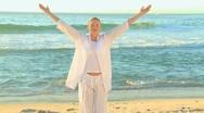 Woman doing yoga on a beach Stock Footage