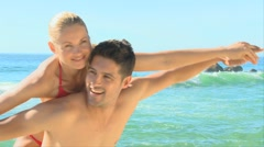 Couple pretending to fly on a beach Stock Footage