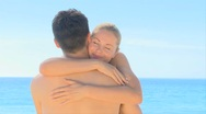 Attractive  woman hugging boyfriend on a beach Stock Footage