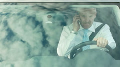 Manager driving car and talking on cell phone - stock footage