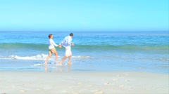 Couple paddling  and playing at the water's edge Stock Footage