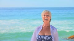 Mature woman dancing on a beach Stock Footage