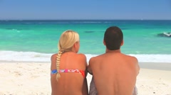 Young man sitting on a beach with his arm around his girlfriend Stock Footage