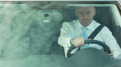 Businessman driving car with sky reflections on windshield Stock Footage