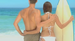 Couple holding a surf board and looking at the sea - stock footage
