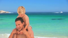 Well-built man holding his son on his shoulders Stock Footage