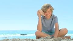 Young smiling boy listening to a shell Stock Footage