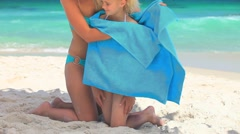Blonde woman drying her daughter ater a swim - stock footage