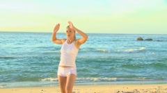 Woman doing stretching excersises on a beach Stock Footage