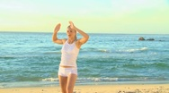 Stock Video Footage of Woman doing stretching excersises on a beach