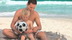 Father and small son sitting on a beach Stock Footage
