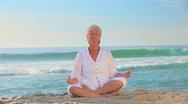 Mature woman in white doing yoga Stock Footage
