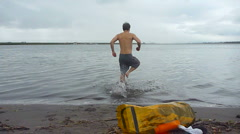 Man Jumping into Freezing Cold Water Stock Footage