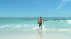 Man with surf board  getting out of the water - stock footage