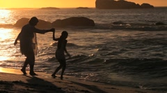 Elderly woman and her grandaughter on the beach at sunset Stock Footage