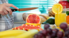 Woman hands cutting grapefruit - stock footage
