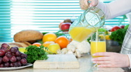 Female hand pouring orange juice Stock Footage