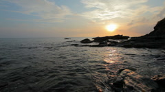 Sunset over rocky coast - stock footage