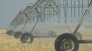 Center pivot irrigation system slowly crawls across dry field Stock Footage