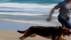Young Man and Dog Run On Beach - stock footage