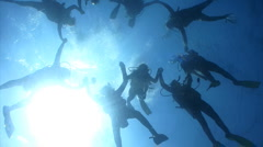 Scuba Divers holding hands forming a circle - stock footage