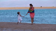 Mother and child walk on the beach Stock Footage