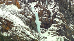 Icy Waterfall on Rocky Mountain with Forest (technicolor edit) Stock Footage